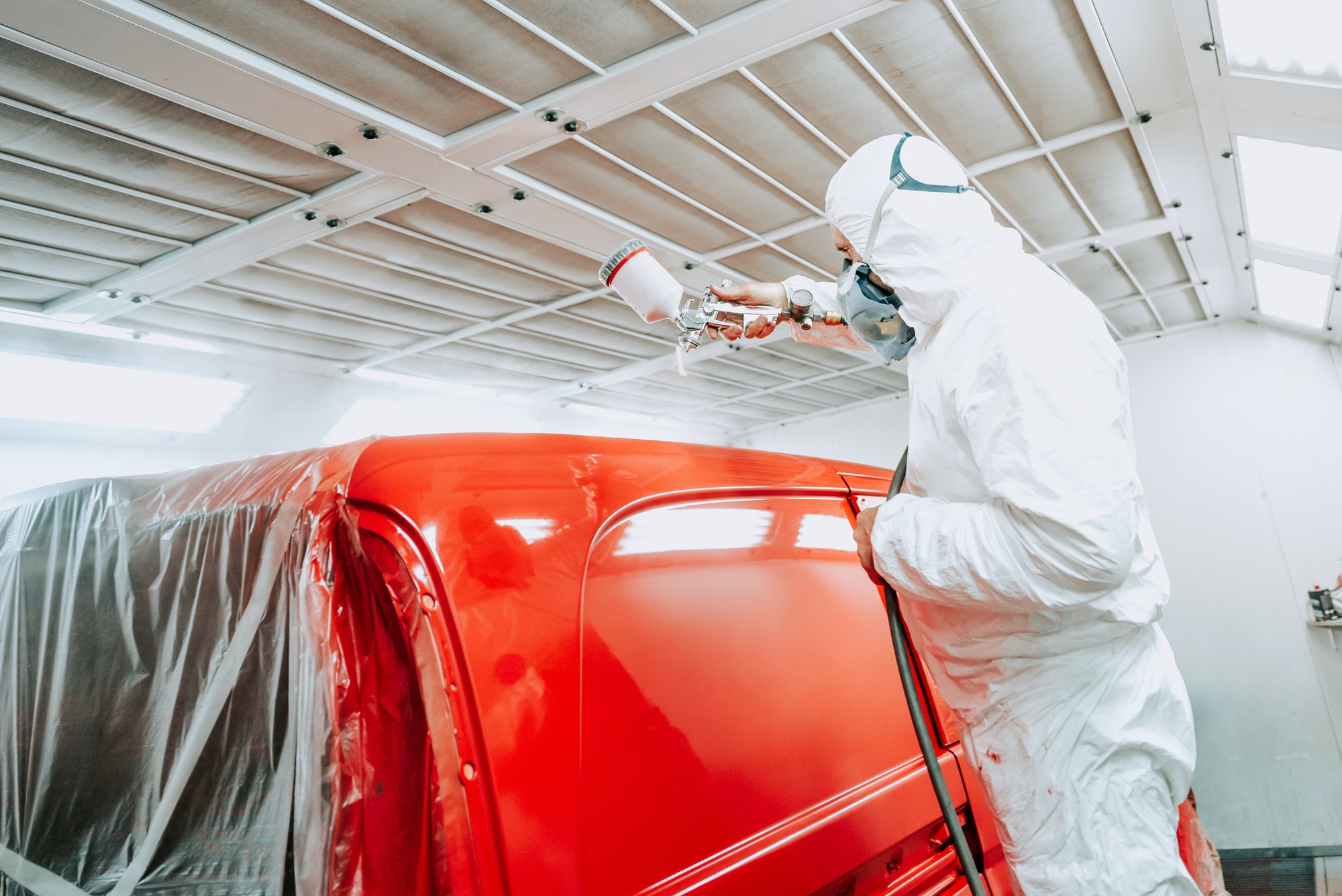 Auto painter spraying red paint on van, car in auto workshop