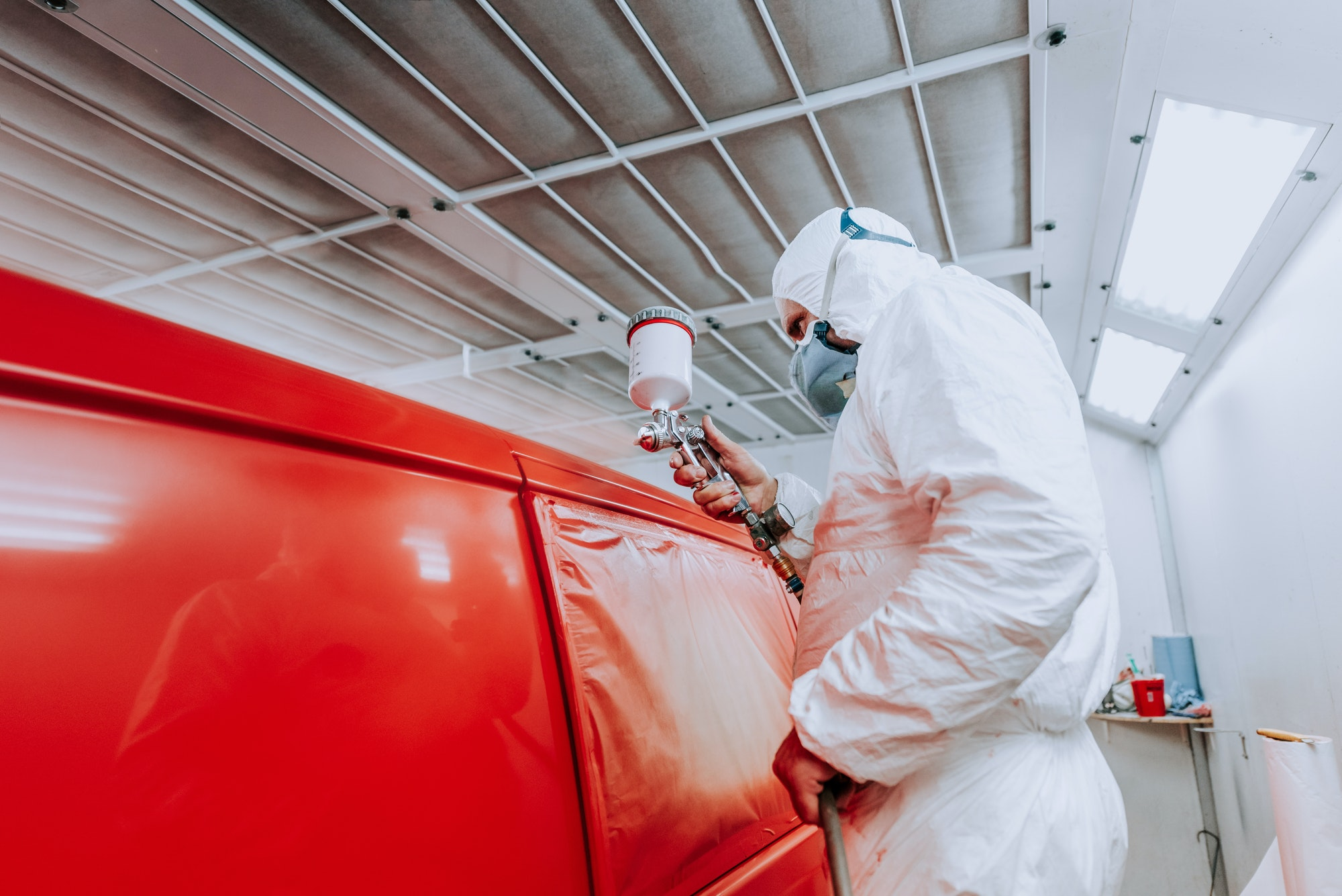 Details of automotive engineer, mechanic painting a red car in workshop