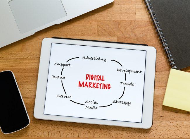 Mesa de trabajo con tableta digital que muestra el concepto de marketing digital