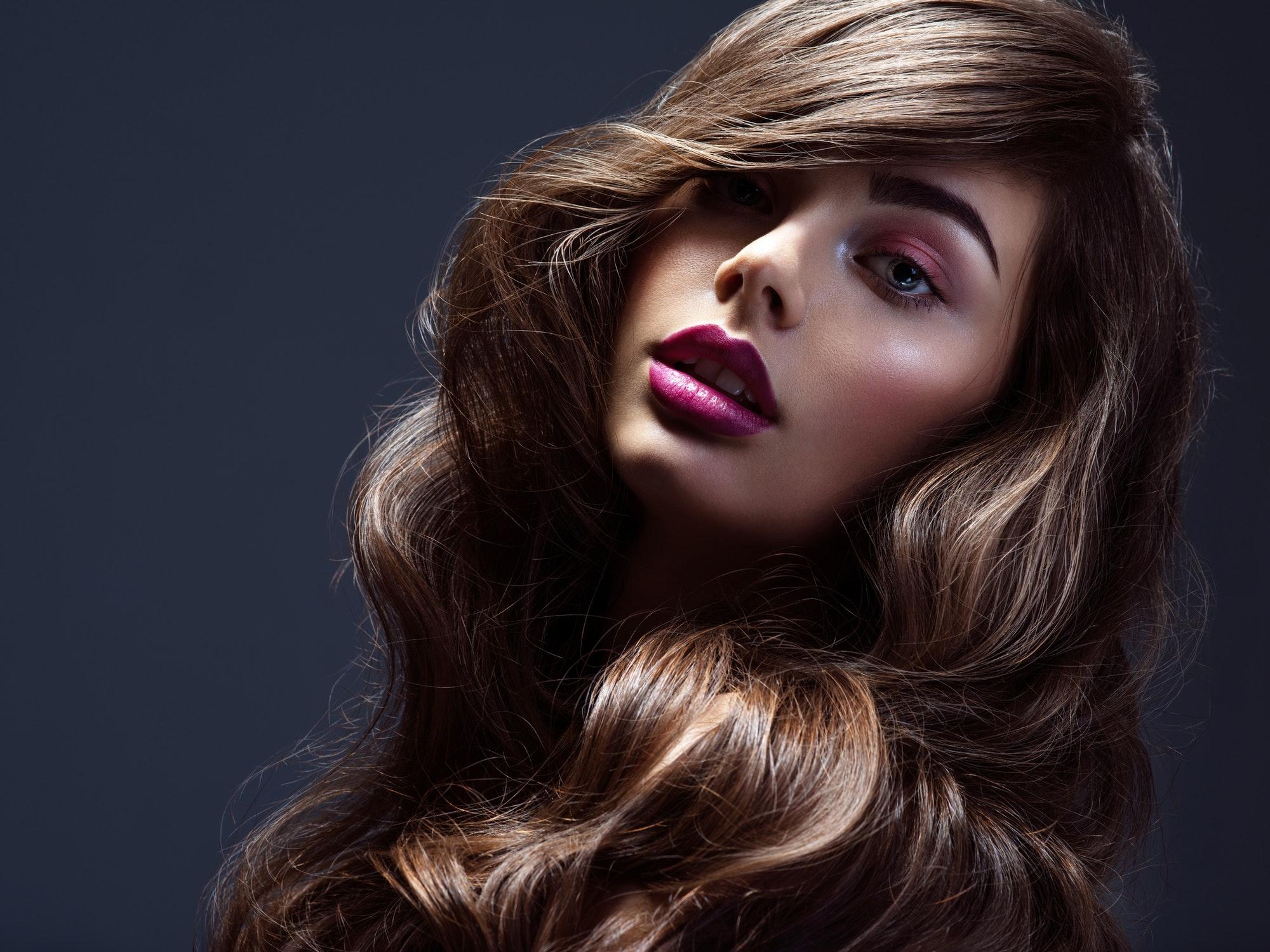 Rostro de una bella mujer con cabello largo y rizado castaño. Modelo de moda con peinado ondulado.